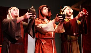 """Tom Hagaman, Corbin Delgado and Payton Brasher present their gifts in """"The Play of Herod."""" The collection of manuscripts used is known as the Fleury Playbook, and is among the most comprehensive notation for early liturgical musical material from around 1200 A.D. Photo credit: Shylee Garrett/Observer Staff"""