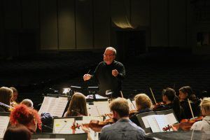"""Photo by Linnea Ritchie. Daniel Culver conducts the Augustana Symphony Orchestra during rehearsal on Dec. 1. The orchestra will perform on Dec. 5 and 6 during the """"Christmas at Augustana"""" annual concert. It will perform alongside other Augustana ensembles, including the Wennerberg Men's Chorus and the Augustana Brass Ensemble."""
