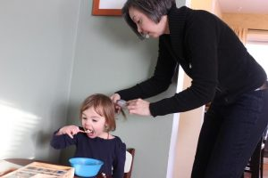 Jennifer Popple brushes her daughter, Anya's hair while eating breakfast and getting ready for school. Popple has two children with Samantha Keehn, a professor in the music department.  Photo by Madison Rodgers.