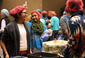 Augustana students and members of the Quad Cities community volunteer to package food for Syrian refugees at the Waterfront Convention Center in Bettendorf on Dec. 5. Photo by Marlen Gomez.